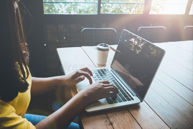 Seitenansicht des reizend jungen Hippie-Mädchens übergibt das Arbeiten an ihrem Laptop, der am Holztisch in einer Kaffeestube sit stockfotografie