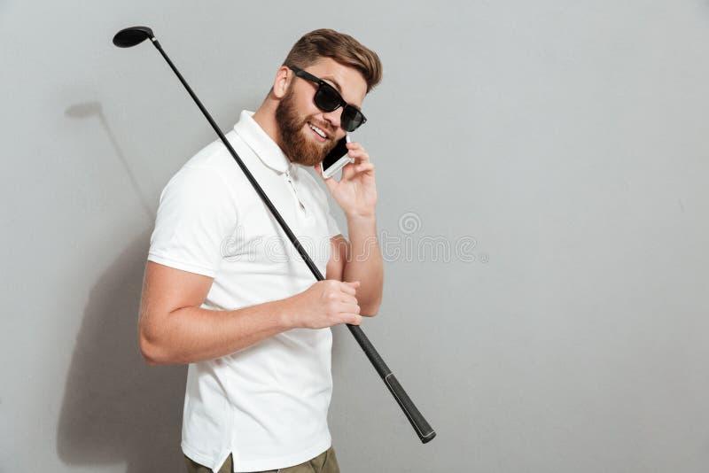 Seitenansicht des ruhigen Golfspielers in der Sonnenbrille sprechend durch Smartphone stockfotos