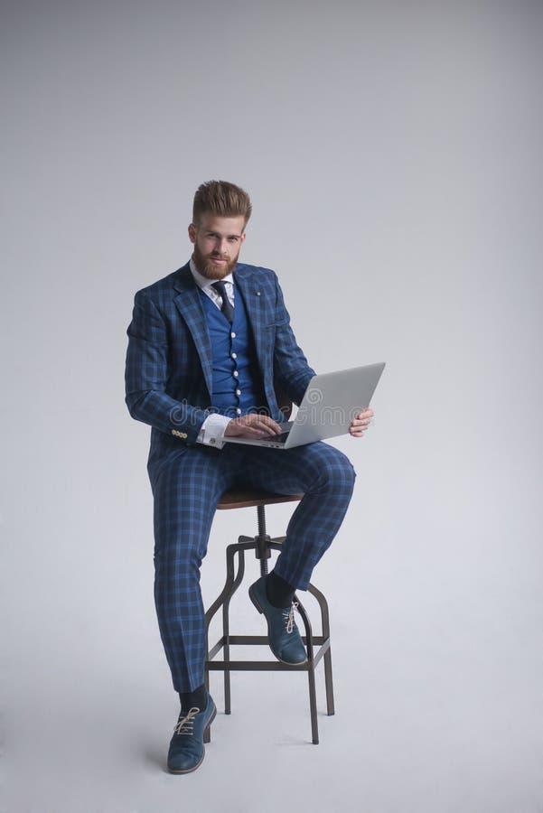Seitenansicht des starken Gesch?ftsmannes im Lehnsessel, der an Laptop arbeitet angekleidet in der Klage mit drei Stücken lizenzfreie stockbilder