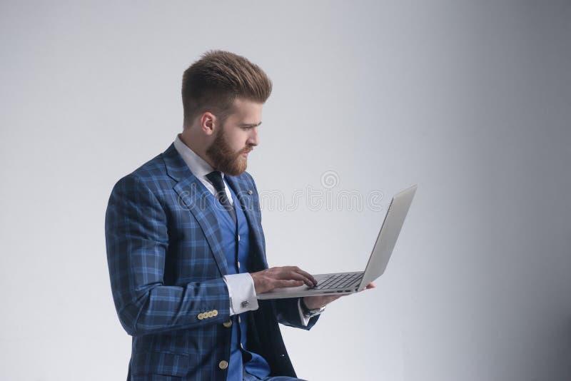 Seitenansicht des starken Gesch?ftsmannes im Lehnsessel, der an Laptop arbeitet Auf Grau lizenzfreies stockfoto