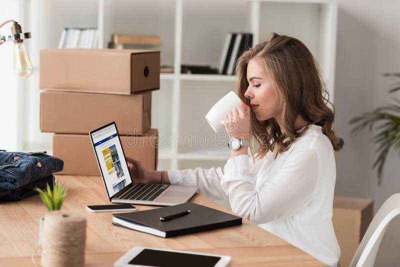 Seitenansicht des trinkenden Kaffees der Geschäftsfrau beim Arbeiten an Laptop stockfotografie