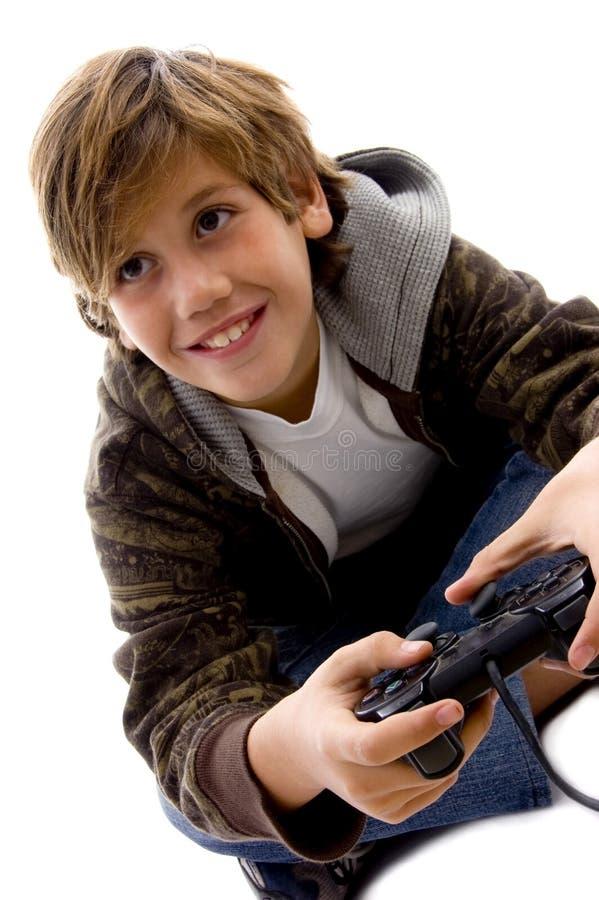 Seitenansicht des unterhaltenen Jungen, der Videospiel spielt stockbild