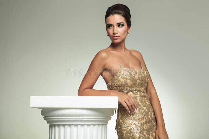 Seitenansicht einer Frau im Kleid, das auf Spalte sich lehnt lizenzfreies stockfoto