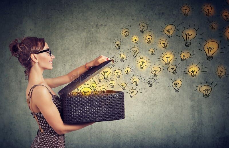 Seitenansicht einer Frau mit dem Kasten voll von den glänzenden Ideen, die kreativ sind stockfotografie