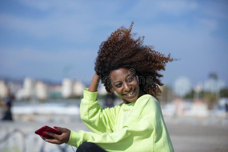 Seitenansicht einer jungen gelockten Afrofrau, die auf dem genie?enden und l?chelnden Wellenbrecherrock w?hrend unter Verwendung  lizenzfreie stockbilder