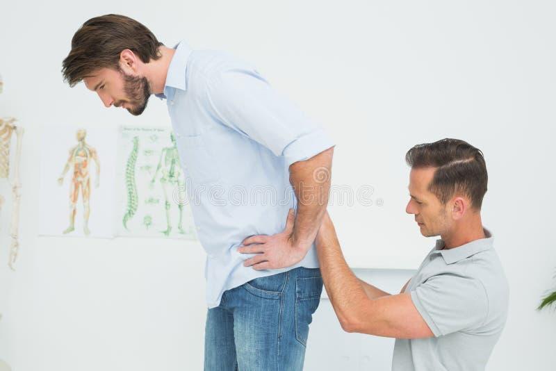 Seitenansicht einer männlichen Physiotherapeutenuntersuchung bemannt zurück stockbild