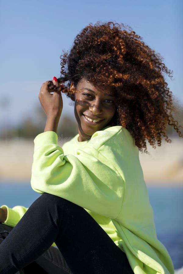 Seitenansicht einer sch?nen gelockten Afrofrau, die auf den lachenden Wellenbrecherfelsen beim Kamera drau?en schauen sitzt lizenzfreie stockbilder