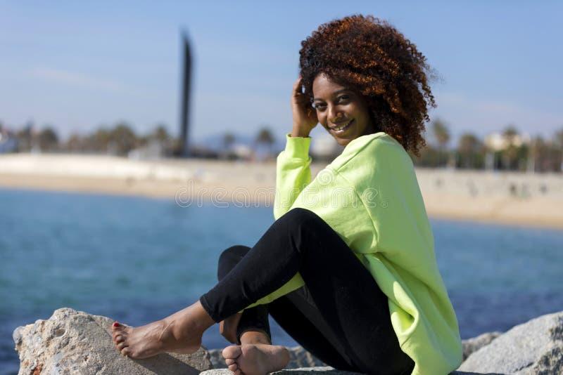 Seitenansicht einer sch?nen gelockten Afrofrau, die auf den lachenden Wellenbrecherfelsen beim Kamera drau?en schauen sitzt stockfotografie