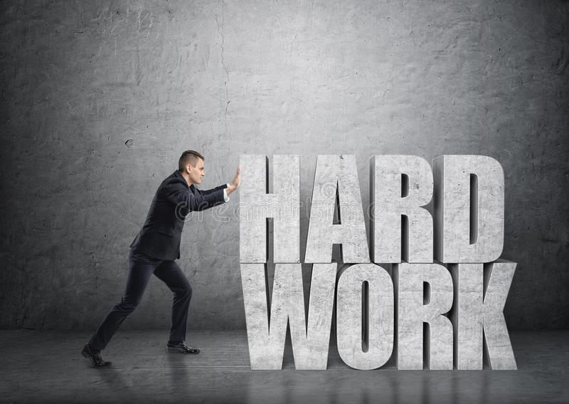 Seitenansicht eines Geschäftsmannes, der großen Beton 3d u. x27 drückt; hartes work& x27; Wörter stockfotos