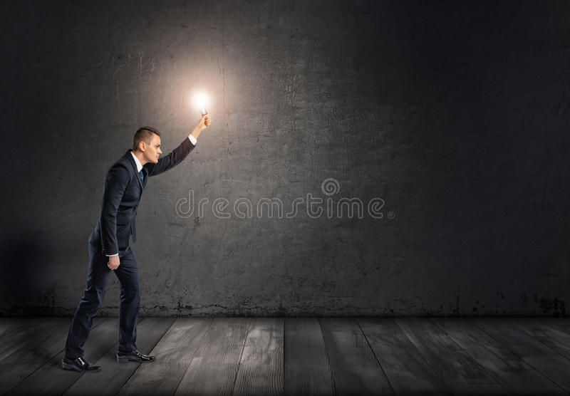 Seitenansicht eines Geschäftsmannes mit glühender Glühlampe im ausgestreckten Arm, der Dunkelheit durchläuft lizenzfreie stockfotos