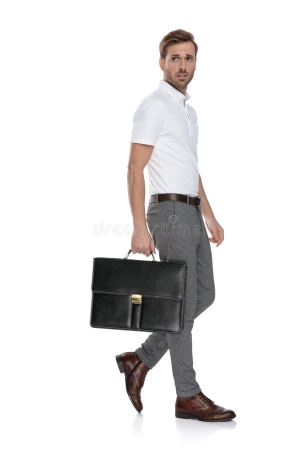 Seitenansicht eines intrigierten Mannes, der mit seinem Koffer geht stockbild
