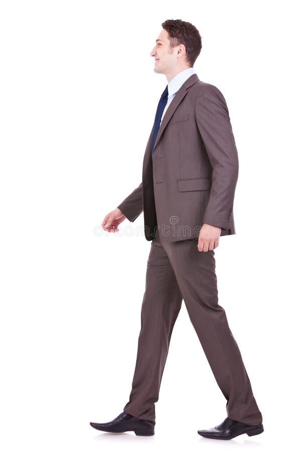 Seitenansicht eines jungen Geschäftsmanngehens stockbilder