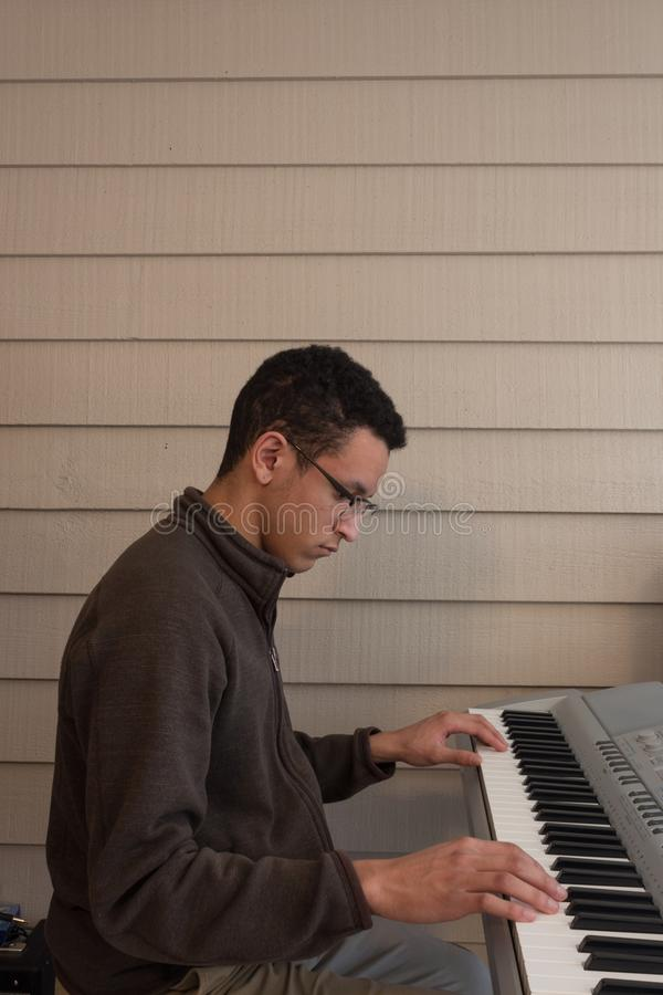 Seitenansicht eines jungen Mannes, der weit eine elektrische Tastatur, Hände auseinander, unten schauend spielt lizenzfreie stockfotos