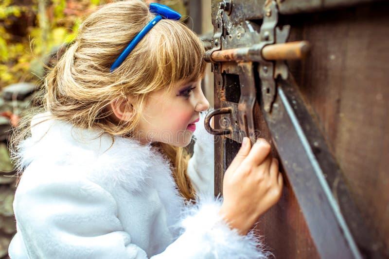 Seitenansicht eines kleinen schönen Mädchens in der Landschaft von Alice im Märchenland, das das Schlüsselloch des Tors untersuch stockfotografie