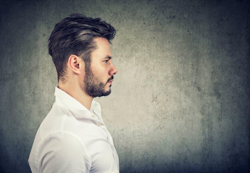 Seitenansicht eines modernen Mannes im weißen Hemd, das auf grauem Hintergrund ernst schaut lizenzfreie stockbilder