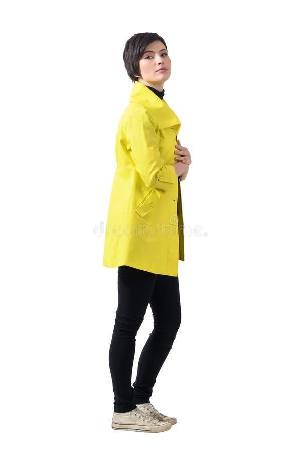 Seitenansicht recht weiblichen kurzes Haar Brunette, der gelben Mantel trägt lizenzfreies stockbild