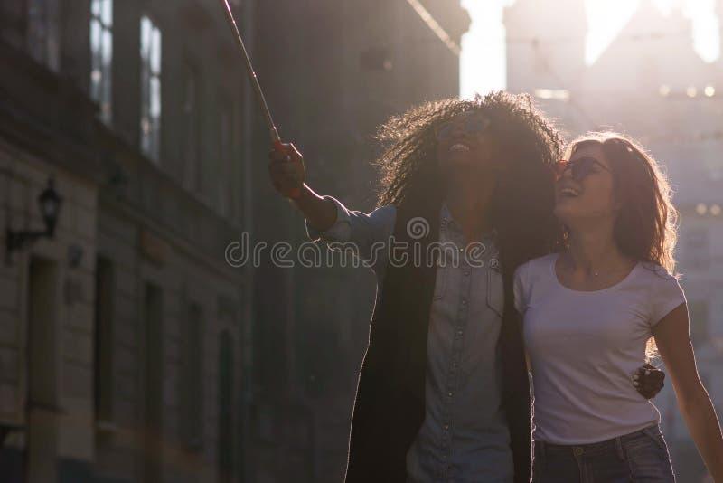 Seitenansicht schönen afroen-amerikanisch Brunette zwei und kaukasischen blonden der Freundinnen, die selfies unter Verwendung lä lizenzfreie stockfotos
