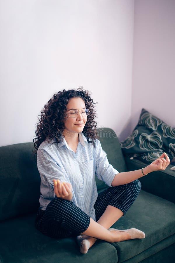 Seitenansicht schoss von der dünnen Frau, die zuhause meditiert stockfoto