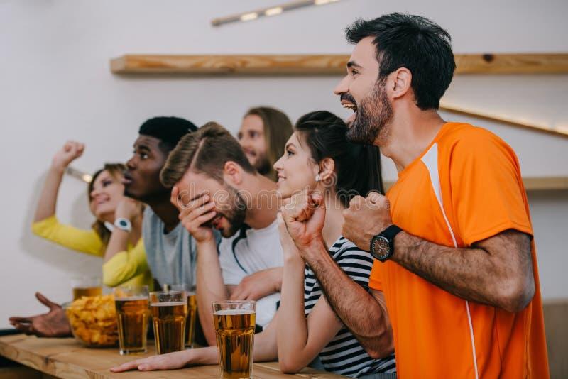 Seitenansicht von den emotionalen multikulturellen Freunden, die durch Hände und aufpassendes Fußballspiel an der Bar mit Bierglä lizenzfreie stockbilder