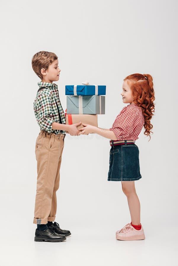 Seitenansicht von den entzückenden glücklichen Kindern, die Geschenke halten stockfoto