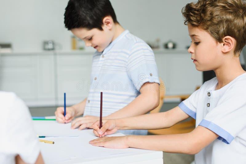 Seitenansicht von den kleinen Brüdern, die bei Tisch Bilder zeichnen stockbilder