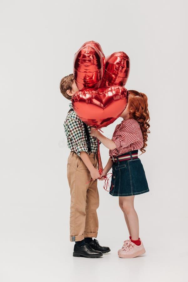 Seitenansicht von den schönen kleinen Paaren, die mit Herzen stehen, formte Ballone stockfoto