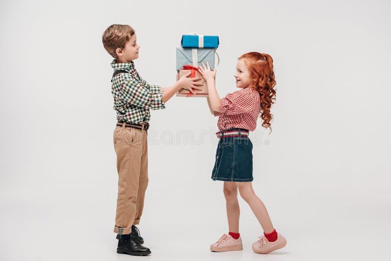 Seitenansicht von den schönen lächelnden Kindern, die Geschenke halten lizenzfreie stockbilder