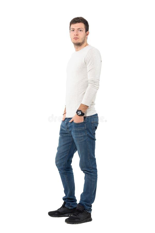 Seitenansicht von den tragenden Jeans und von Turnschuhen des jungen ernsten zufälligen Mannes, die Kamera betrachten stockbilder