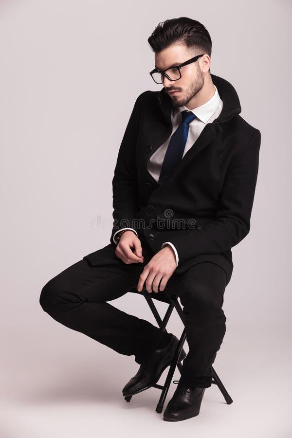 Seitenansichtbild eines jungen eleganten Geschäftsmannsitzens stockfotos