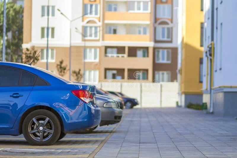 Seitenansichtdetail der Autoreihe geparkt in gepflastertem YardParkplatzbereich auf unscharfem errichtendem Hintergrund am hellen lizenzfreies stockbild