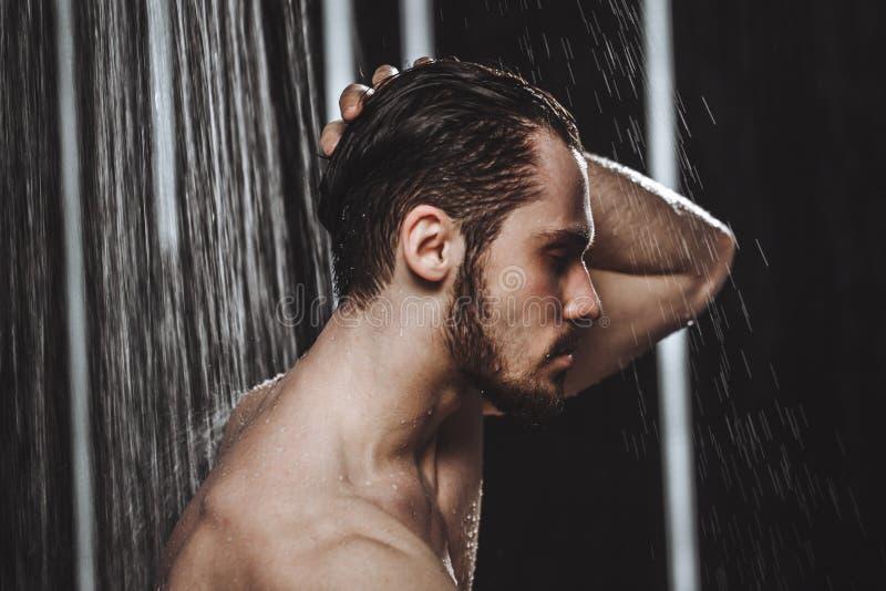 Seitenansichtfoto der Nahaufnahme eines jungen Mannes, der eine Dusche nimmt lizenzfreies stockbild