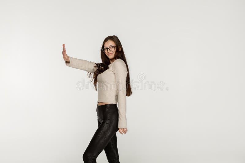 Seitenansichtfoto des frohen glücklichen europäischen Mädchens mit dem langen brunette Haar, das schwarze Gamaschen und Gläser tr lizenzfreies stockbild