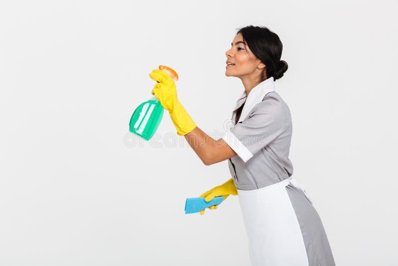 Seitenansichtfoto des jungen Mädchens in der grauen Uniform, die das saubere sprüht lizenzfreies stockbild