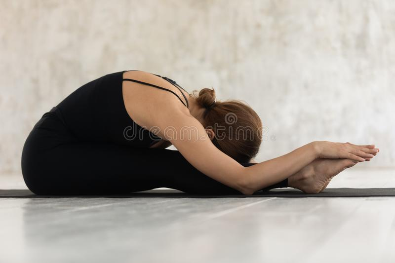 Seitenansichtfrau, die Sitzrumpfbeugehaltung auf Matte tut lizenzfreie stockfotos