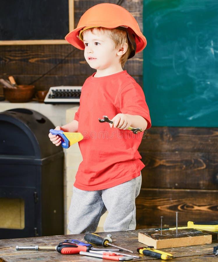 Seitenansichtkind, das in der Werkstatt steht Blonder Junge im orange Sturzhelm, der Schlüssel und Handsaw hält Kleiner Schlosser lizenzfreie stockfotos