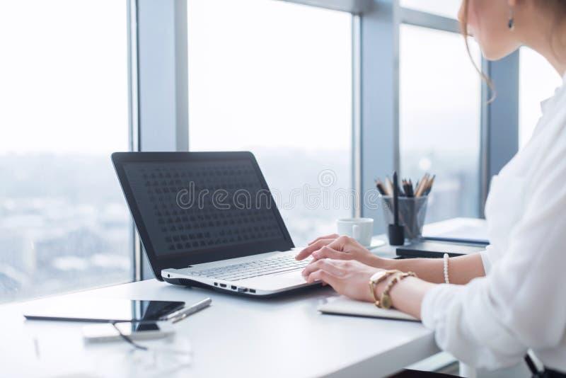 Seitenansichtporträt der Frau arbeitend im Hausbüro als Tele-Arbeiter, Schreiben- und Surfeninternet, Arbeitstag habend lizenzfreie stockfotografie
