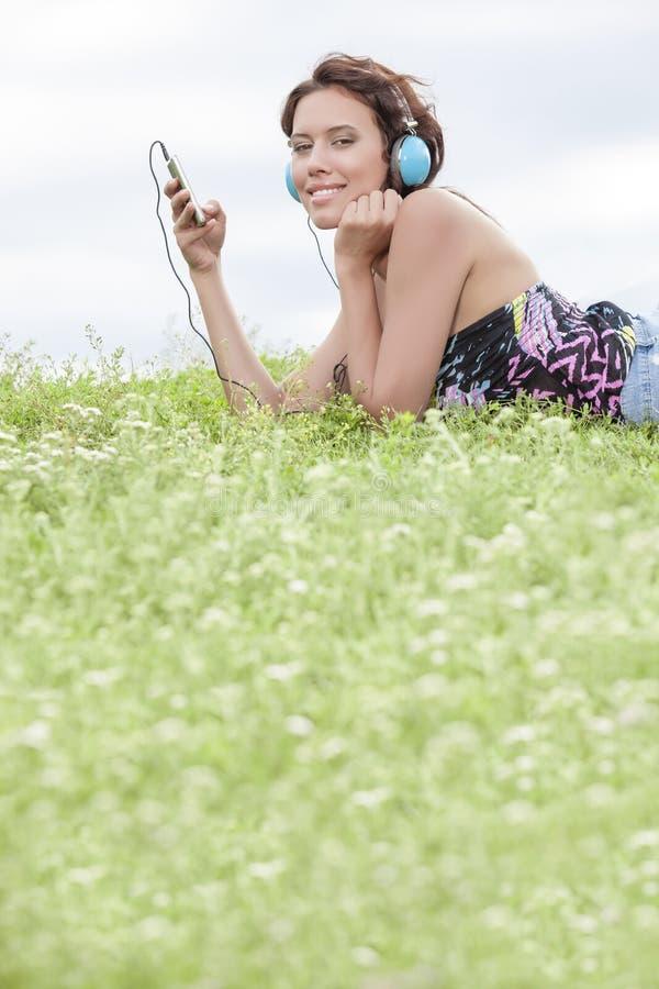 Seitenansichtporträt der Frau hörend Musik durch Handy unter Verwendung der Kopfhörer beim Lügen auf Gras gegen Himmel stockbilder