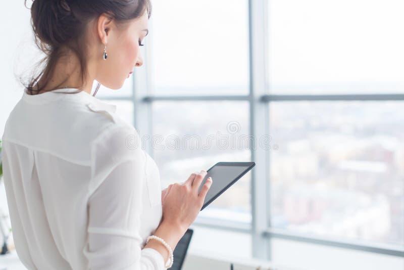 Seitenansichtporträt der Nahaufnahme eines Angestellten, der Mitteilungen während ihres Bruches am Arbeitsplatz simst, sendet und lizenzfreies stockbild