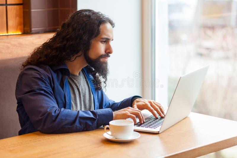 Seitenansichtporträt des jungen erwachsenen Mannfreiberuflers der hübschen Intelligenz in der zufälligen Art, die im Café sitzt u lizenzfreie stockbilder