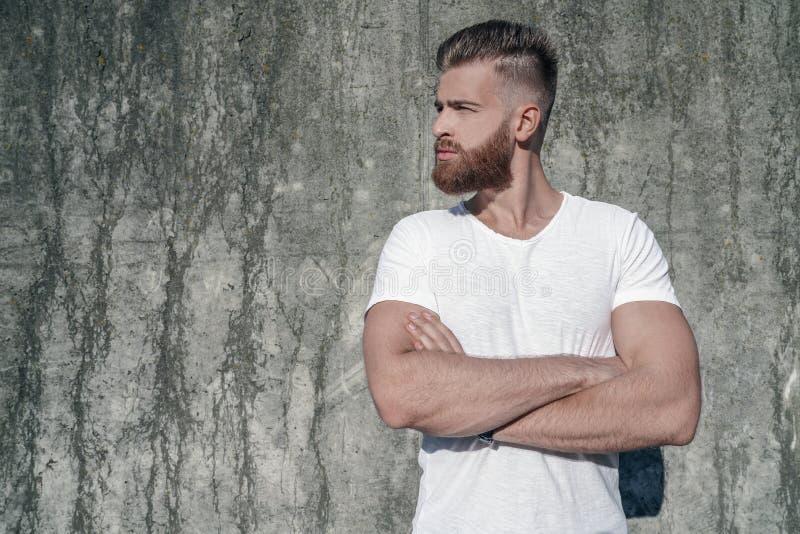 Seitenansichtporträt des jungen schönen bärtigen Kerls, der draußen gegen die graue moderne Dachbodenwand beiseite schaut mit sei stockbilder