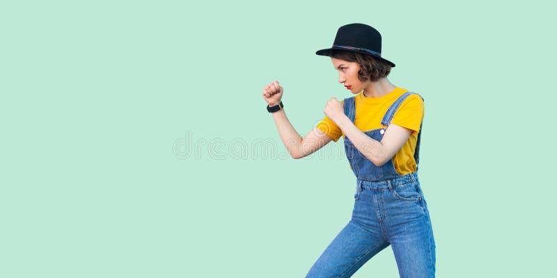 Seitenansichtporträt des Profils des ernsten jungen Mädchens im blauen Denimoverall, gelbes Hemd, Stellung des schwarzen Hutes mi stockfotos
