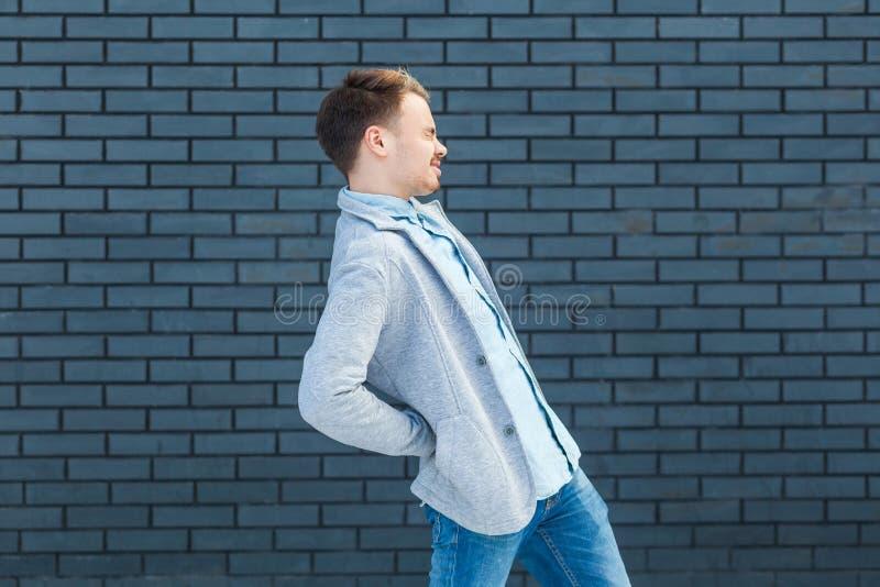 Seitenansichtporträt des Rückseiten- oder Nierenschmerzprofils des kranken oder müden hübschen jungen blonden Mannes in der zufäl lizenzfreie stockfotos