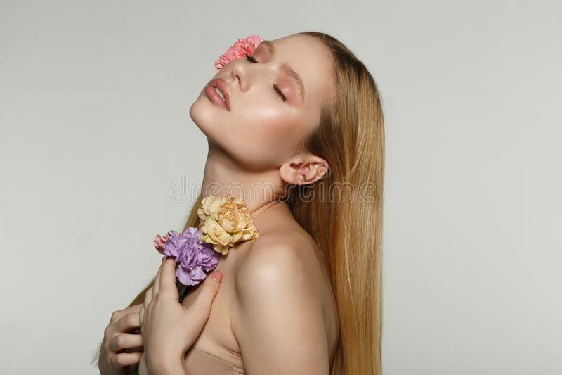 Seitenansichtporträt des reizend jungen blonden Mädchens mit perfektem Make-up und geschlossenen Augen, drückte Blumen zu ihrem K stockfotografie