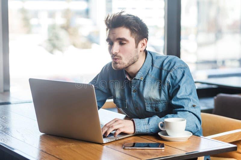 Seitenansichtporträt des reizenden bärtigen jungen gut aussehenden Mannes im Blue Jeans-Hemd sitzen allein im Café und machen Vid stockfotos