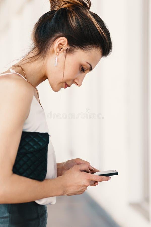 Seitenansichtporträt einer lächelnden eleganten jungen Frau unter Verwendung eines smar stockfotografie