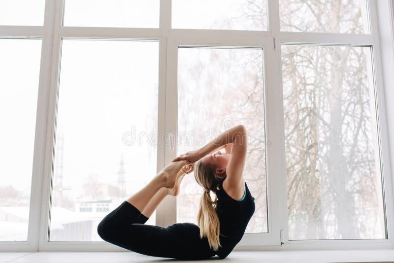 Seitenansichtporträt von den attraktiven jungen Blondinen, die im Fitness-Club oder zu Hause, Yoga tuend ausarbeiten oder pilates lizenzfreie stockfotos