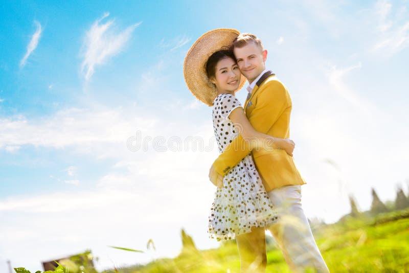 Seitenansichtporträt von den romantischen Paaren, die auf Feld gegen Himmel umfassen lizenzfreies stockbild