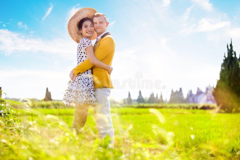 Seitenansichtporträt von den romantischen Paaren, die auf Feld umfassen stockbilder