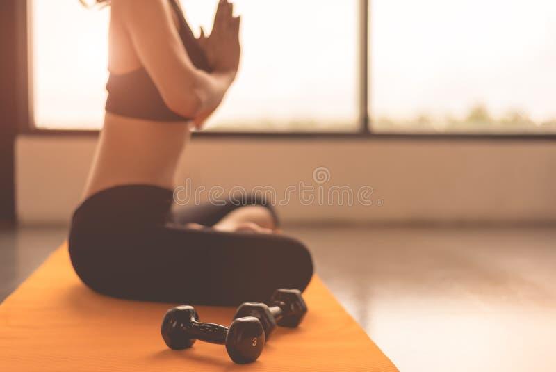 Seitenansichtsch?nheitsfrau, die Yoga und Hand anheben oder Verbeugung in den Eignungstrainings zahlen ausbilden Turnhallenmitte  stockbilder