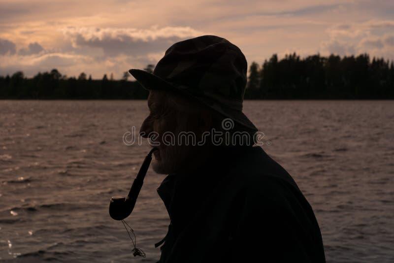 Seitenansichtschattenbild eines alten Fischers, der ein Rohr raucht lizenzfreies stockbild